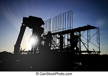 silhouetteConstruction workers work in preparation for...