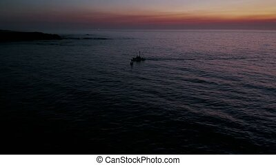 Silhouetted fishing boat returning to harbor after the day`s catch. Aerial sunset.