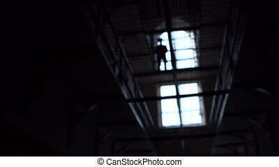 Silhouetted man on jail - A dolly shot worms eye view of...