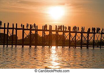 Silhouetted people on U Bein Bridge at sunset, Amarapura,...