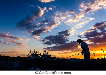 Silhouetted shot of a boy fishing on pier at sunset