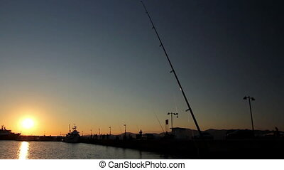 Silhouetted shot of one fishing rod in front of pier at...