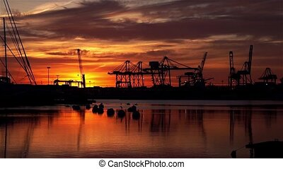 Silhouetted sunrise at the port of Valencia cranes working cargo shipping skyline with clouds reflected in the sea