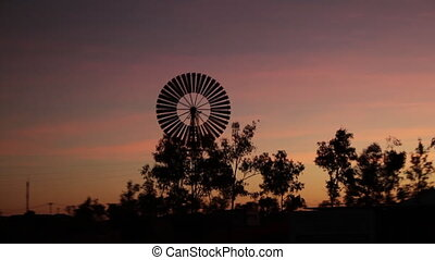 Silhouetted trees and wind mill - A full shot of a wind mill...