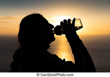 Silhouetted woman drinking water from a bottle