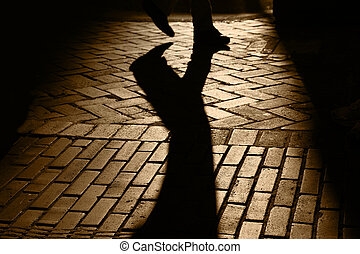 Silhouette and shadows of feet of person walking, brick pavement, San Francisco, California,
