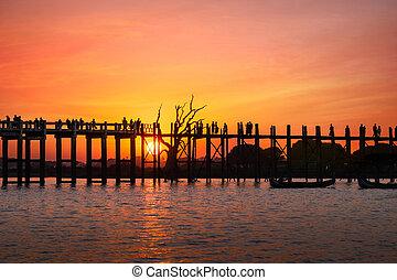 Silhouettes at U Bein teak bridge at sunset. Myanmar (Burma)...