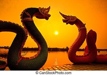 Silhouettes dragon and Naga statue protecting Thai temple