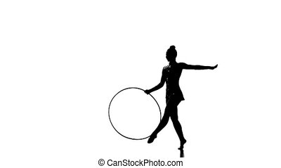 Silhouettes Gymnastic stunt with hula hoop from the beautiful girl, slow motion