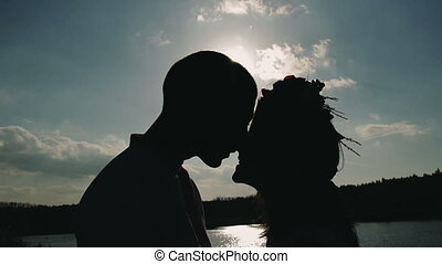 Silhouettes loving couple kissing on nature background