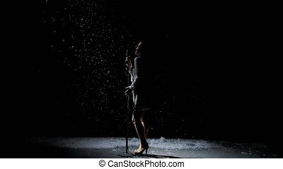 Silhouettes of a beautiful singer with a vintage microphone against the background of falling snow. Snowflakes glisten in studio light. Side view. Slow motion