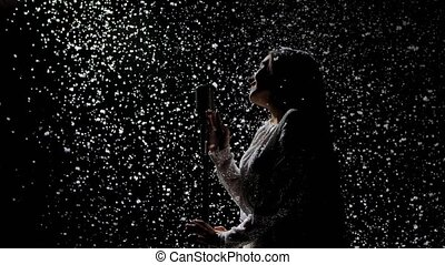 Silhouettes of a beautiful singer with a vintage microphone against the background of falling snow. Snowflakes glisten in studio light. Side view. Slow motion. Close up.