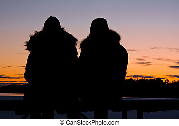 silhouettes of a couple watching the sunset