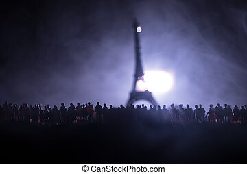 Silhouettes of a crowd standing at field behind the blurred foggy background. Revolution, people protest against government, man fighting for rights