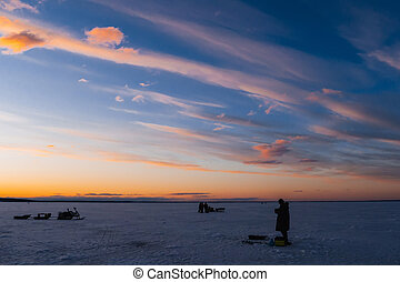 silhouettes of a fisherman with a fishing rod on a winter fishing