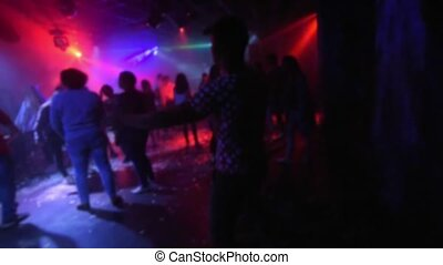 silhouettes of a group of people dancing in a nightclub on...