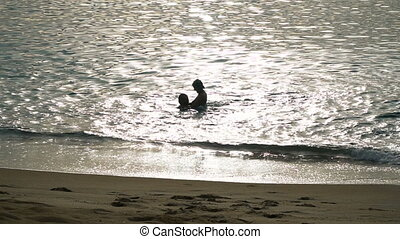 Silhouettes of a happy couple in the sea