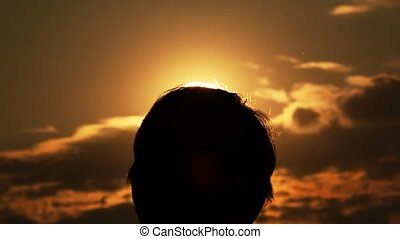 Silhouettes of a head and hands of the man against the sun