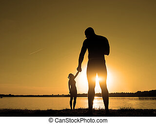 Silhouettes of a loving couple on the beach. Sunset on the beach. Giant and baby