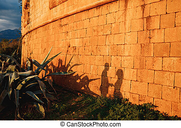 Silhouettes of a man and a woman on the orange wall of an ancient building on a sunny day.