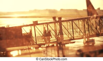 Silhouettes of a passengers walking in a glass jet bridge....