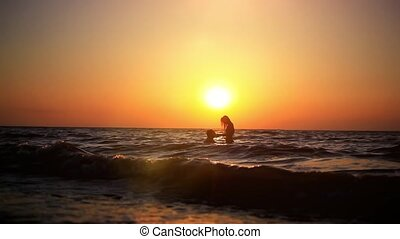 Silhouettes of a swimming couple at amazing sunset. Waves splashed against shore, reflections Of The sun is reflecting in beautiful water. Concept OF tourist holidays