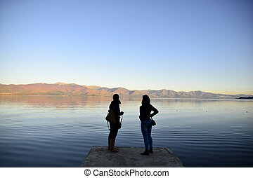 Lake Prespa in Macedonia - Silhouettes of a two girls on a ...