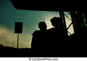 Silhouettes of a wedding couple wathcing the sunset over the highway