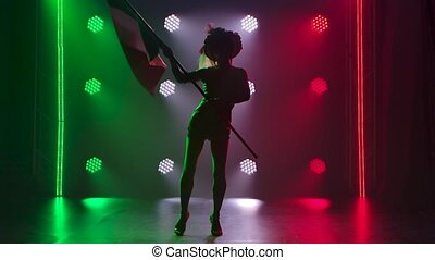 Silhouettes of an attractive woman dancing and waving the Italian flag against a background of green, white and red lights. Theatrical show. Slow motion