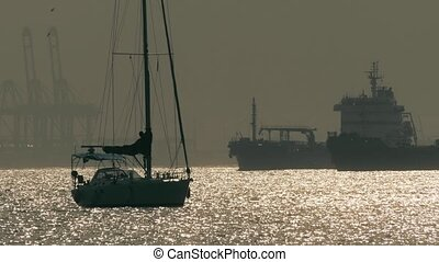 Silhouettes of an unknown anchored sailboat and big cargo...