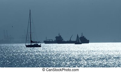 Silhouettes of an unknown sailboats and cargo ships near...
