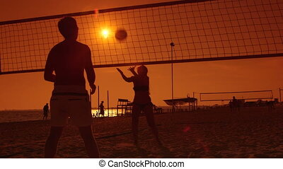 Silhouettes of beach volleyball players at sunset