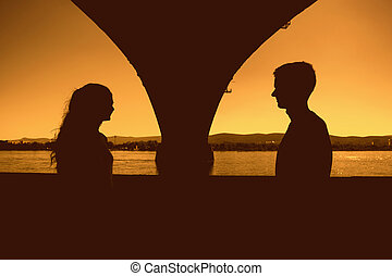 Silhouettes of boy and girl outdoors