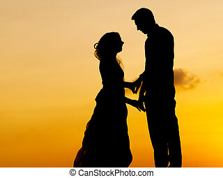 Silhouettes of bride and groom kissing at  sunset.