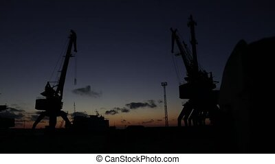 Silhouettes of cargo cranes - Silhouettes of marine cargo...