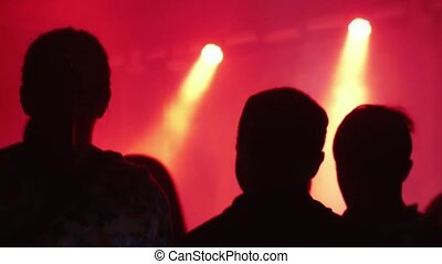 Silhouettes of concert crowd in front of bright stage...