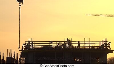 Silhouettes of construction workers against orange sky. 4K...