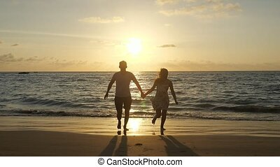 silhouettes of couple running along beach against waves