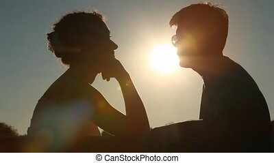silhouettes of couple sits on bench against afternoon sky with sun