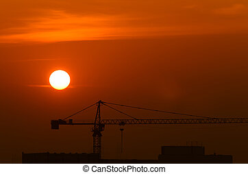 Silhouettes of crane at sunset