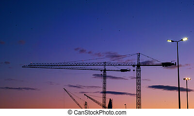 Silhouettes of cranes in the harbor at sunset