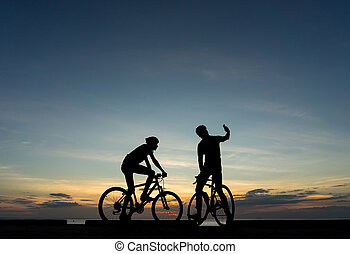 Silhouettes of Cyclists on bicycle at the ocean in the sunset scene selfie action