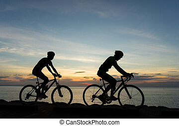 Silhouettes of Cyclists on bicycle at the ocean in the sunset scene