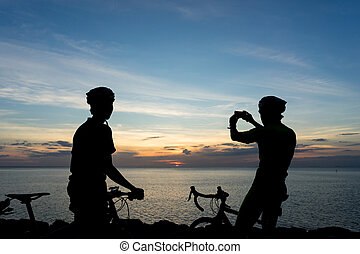 Silhouettes of Cyclists on bicycle at the ocean in the sunset scene taking photograph