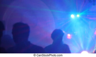 Silhouettes of dancing people in a nightclub