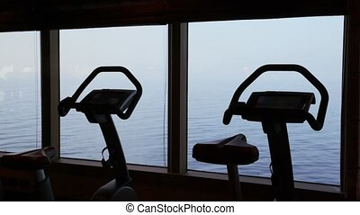 silhouettes of empty exercise bicycles in gym