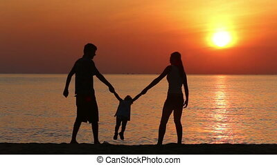 silhouettes of family doing exercises on beach at sunrise