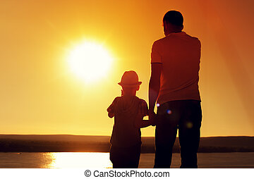 Silhouettes of father and son near sea at sunset - Rear view...