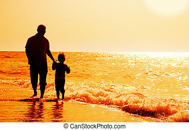 silhouettes of father and son on sunset sea background