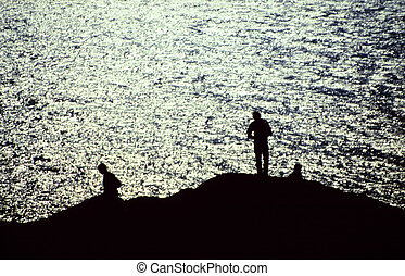 Silhouettes of fishermen by the sea